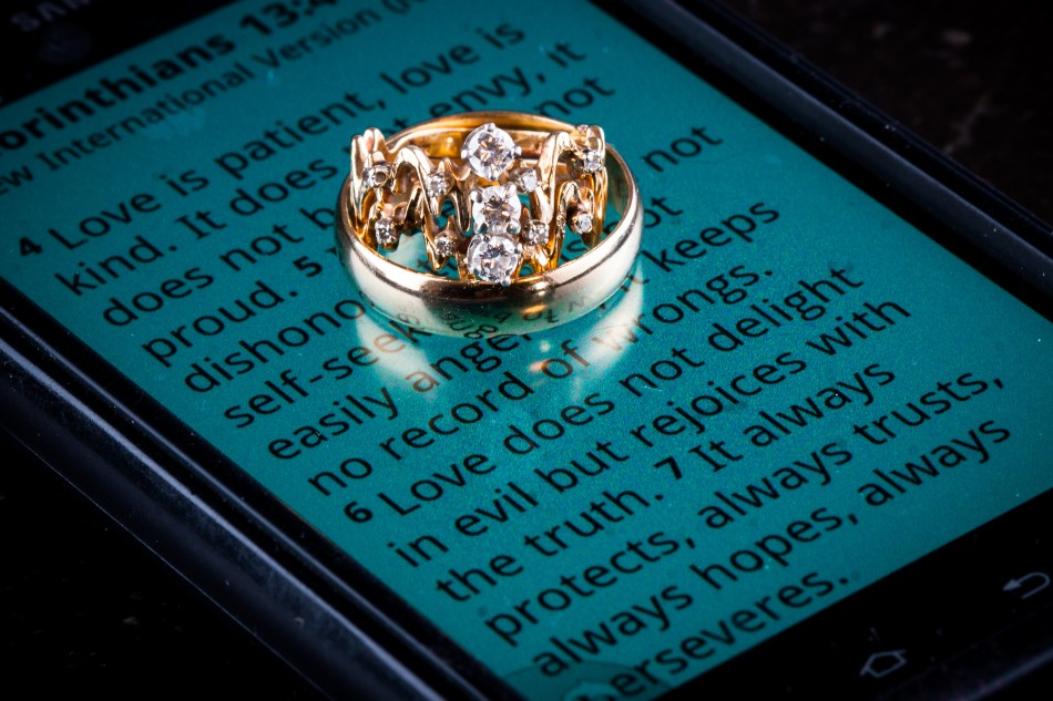 Image of wedding rings on phone showing 1Cor 13
